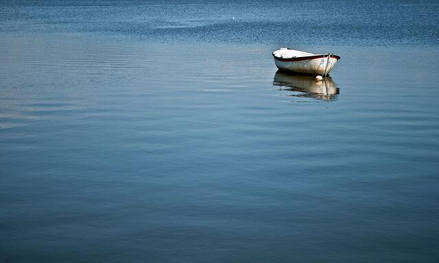 Stock photo of rowboat on calm and peaceful lake.