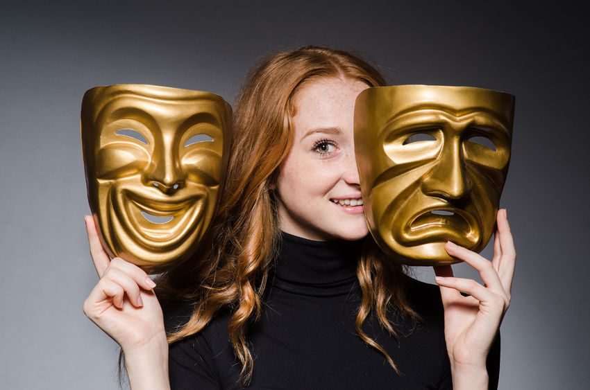 Redheaded woman with theater masks of tragedy and comedy.