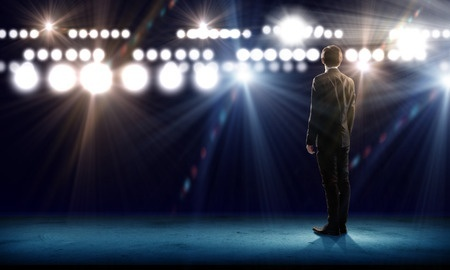 Stock photo of businessman giving a speech with stage lights.