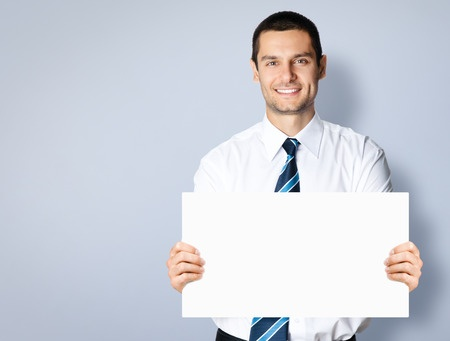 Stock photo of young businessman holding up a sign.