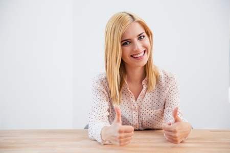 Stock photo of smiling young businesswoman with thumbs up.