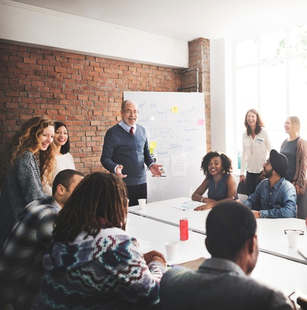 Stock photo of team of employees speaking at a business meeting.
