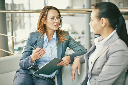Stock photo of two woman in conversation or a dialogue showing eye contact and listening.