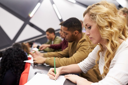 Photo of female taking notes in a university lecture.