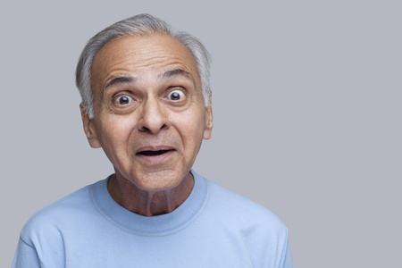 Stock photo of senior Asian man with wide-eyed facial expression.