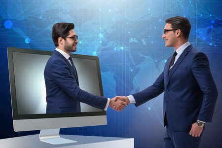 Image of videoconferencing equipment and two men shaking hands.