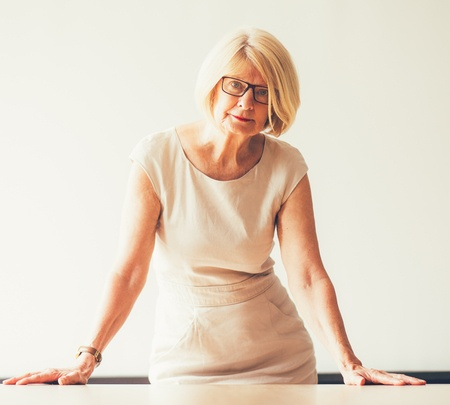 Stock photo of mature business woman in front of whiteboard.