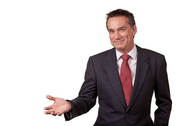Stock photo of businessman gesturing while speaking.