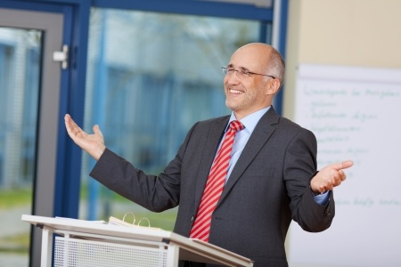 Stock photo of businessman using body language while giving a speech.
