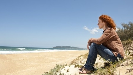Stock photo of red-headed woman on beach.