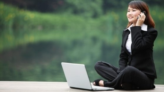 Stock photo of business woman talking on the phone with a laptop.