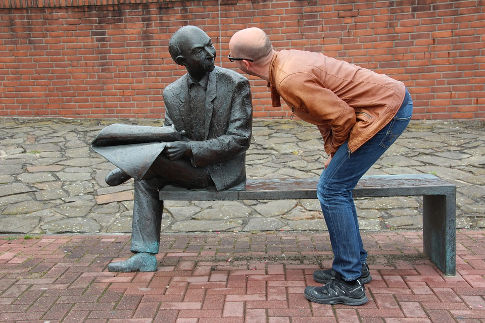 Stock photo of sculpture of a sitting man observed by a bystander.