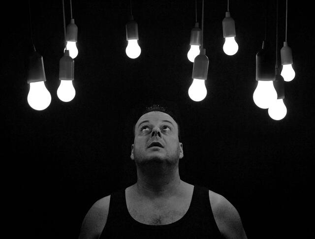 Stock photo image of man looking up at light bulbs in ceiling.
