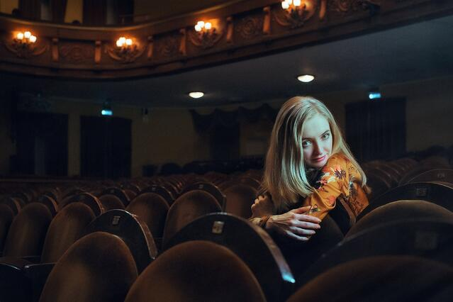 Stock photo of beautiful young woman sitting in audience.