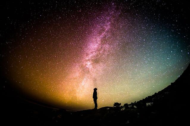 Photo of person standing at night with background of Milky Way Galaxy.
