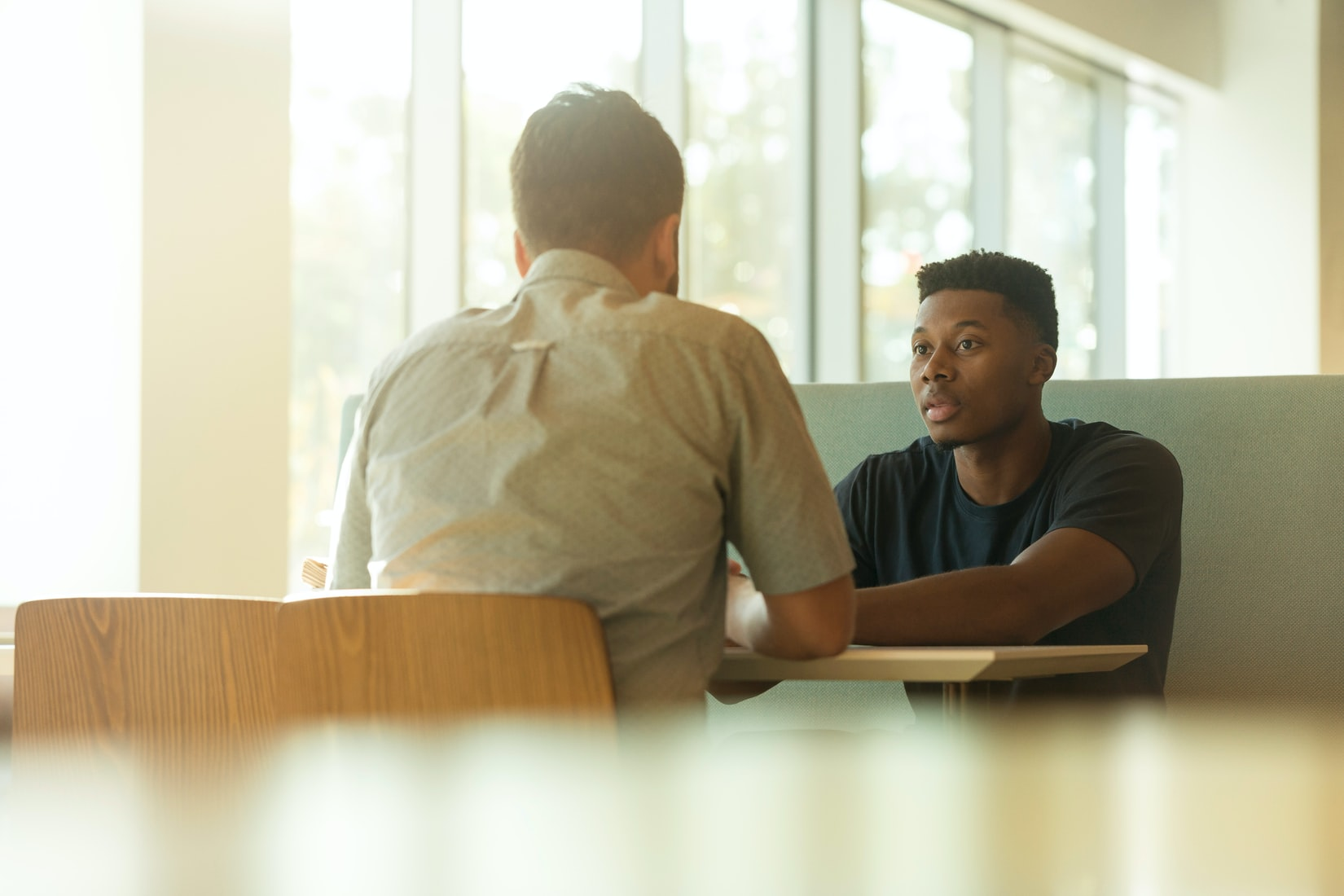 Stock image of Black man and White man having a conversation.