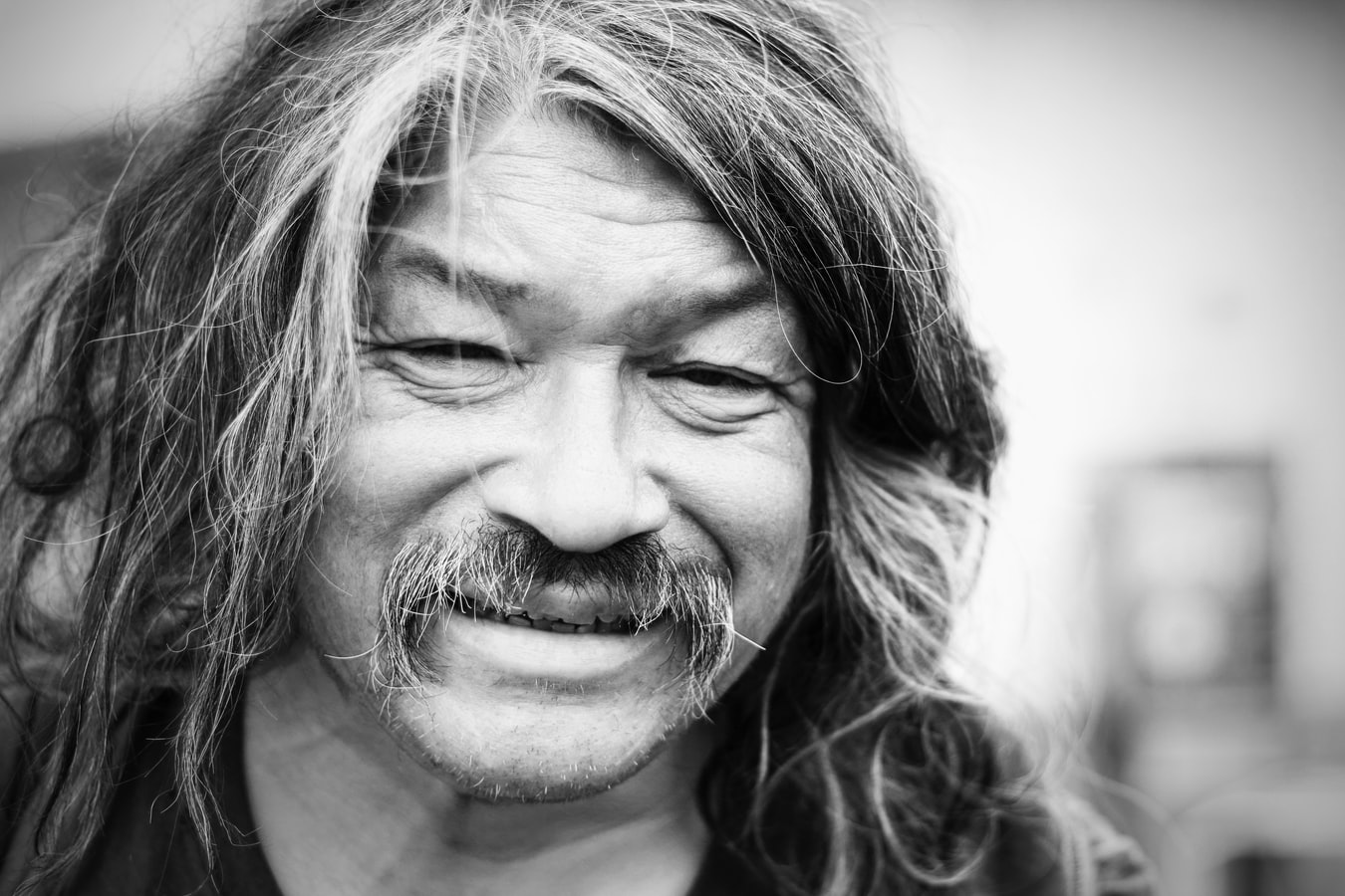 Stock photo of smiling man with long hair and moustache.
