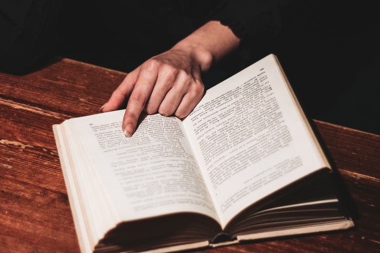 Stock photo of hand pointing to a page in a book.