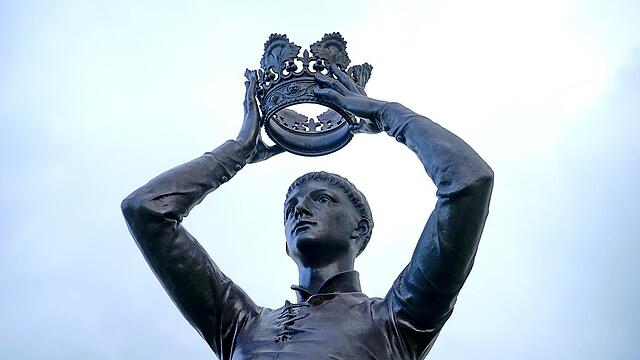 Statue of Shakespeare's Henry V placing crown on his head.