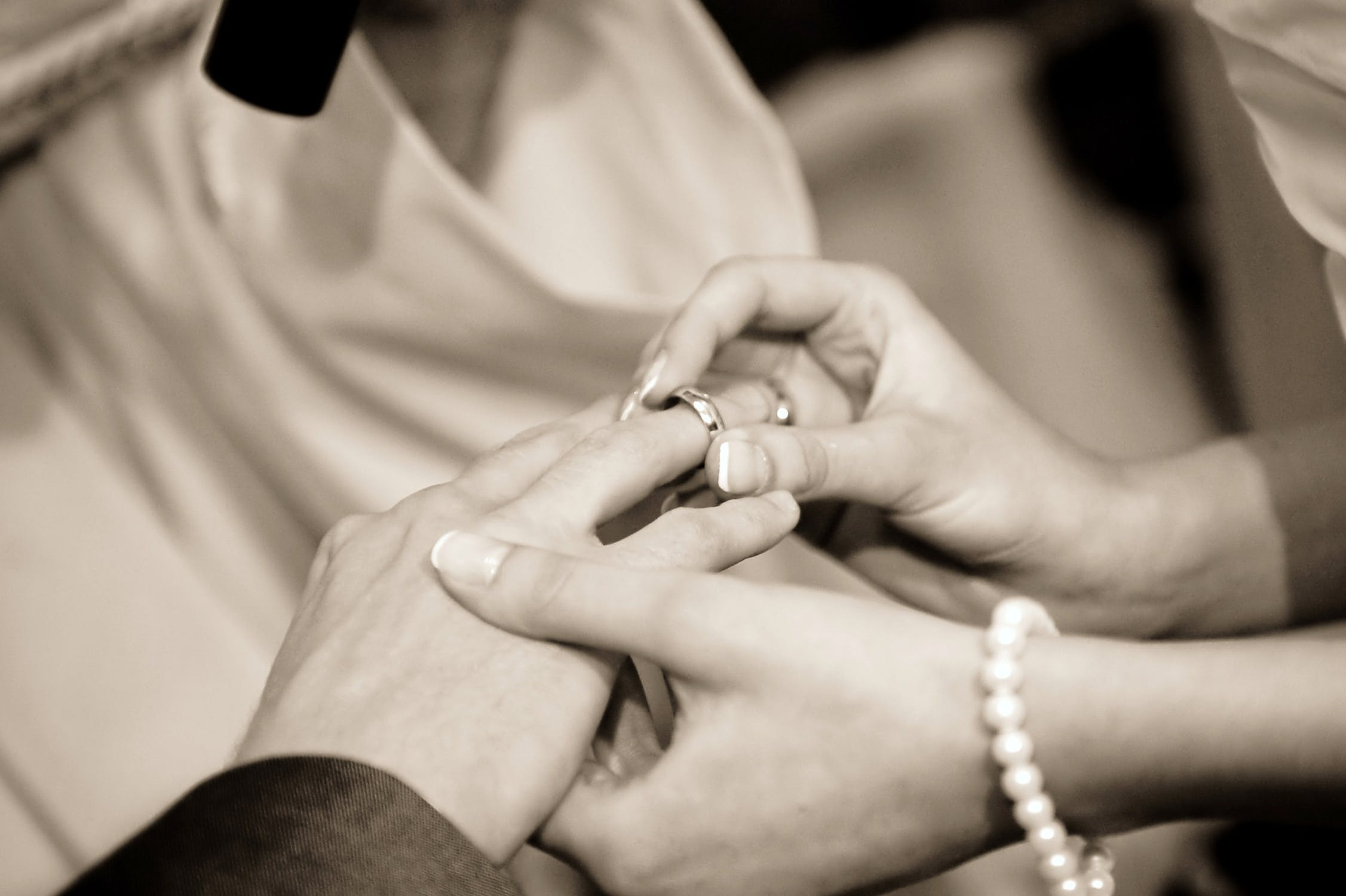 Stock photo of bride placing wedding ring on groom's finger.