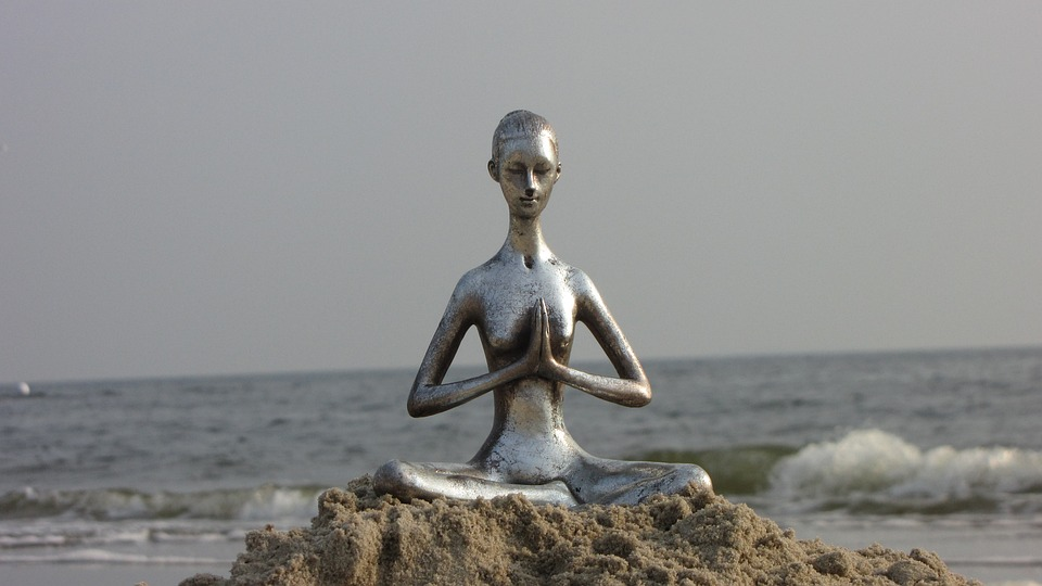 Photo of figure in yoga pose practicing controlled or mindful breathing.