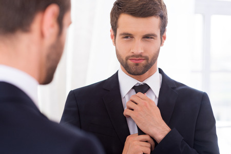 Stock photo of handsome young man with beard looking in the mirror.