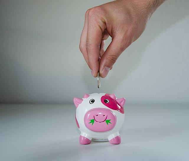 Stock image of man putting money in a piggy bank.